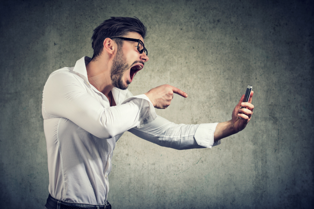 Man yelling into a mobile phone - verbal assault.